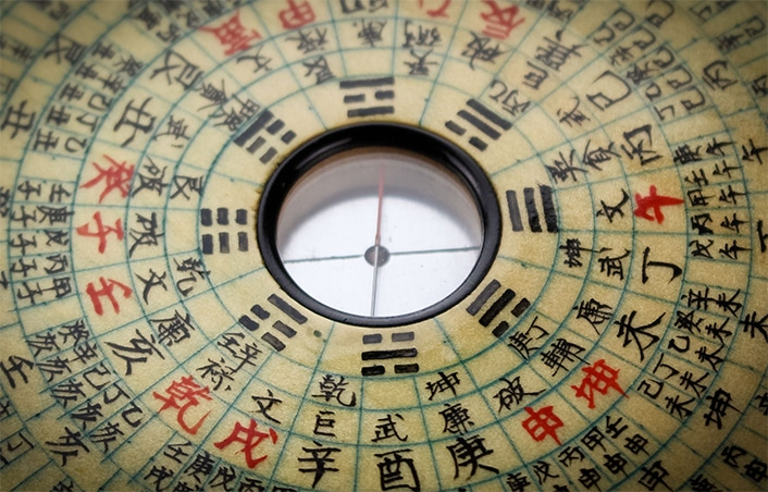 a traditional Chinese astrological compass with red and black Chinese characters on it