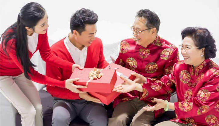 A Chinese family exchanges gifts wrapped in red paper