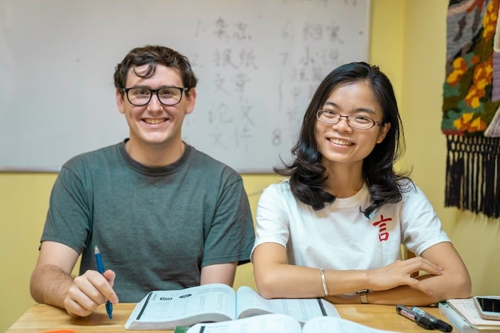 chinese teacher and student in class sitting at wooden table in front of whiteboard