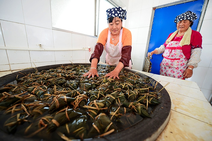 Chinese people making zongzi to celebrate the dragon boat festival