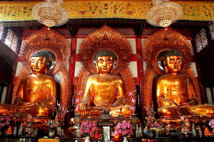 three Buddhist statues in a temple