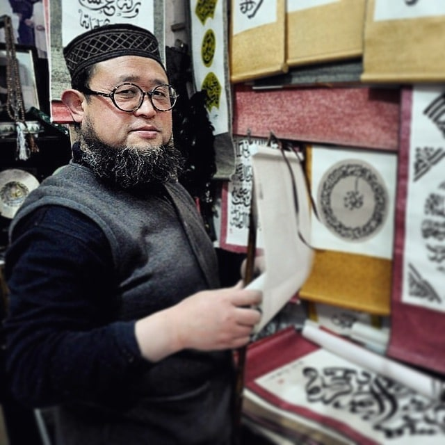 a Chinese Muslim man in a traditional cap standing in front of a wall hung with various scrolls with Arabic writing on them