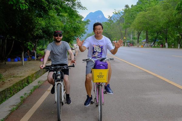 CLI team members ride bikes on a street in Guilin with karst mountains in the background