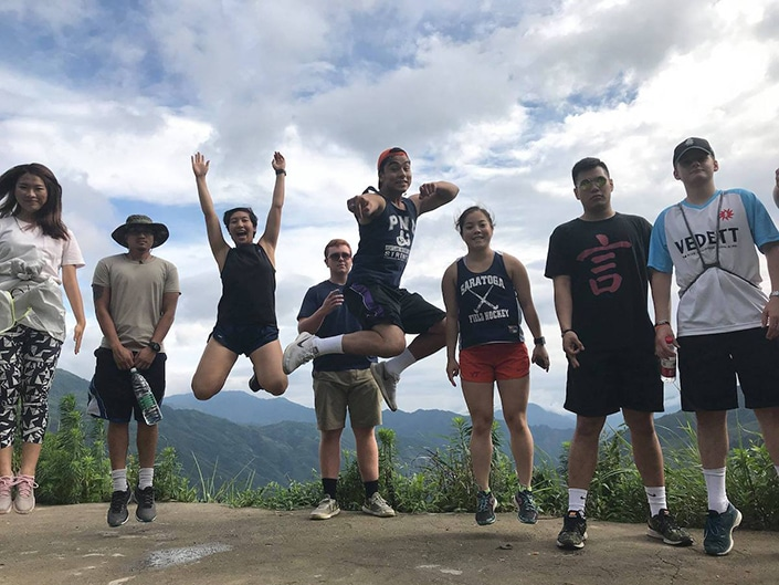 CLI students jump into the air with mountains in the background