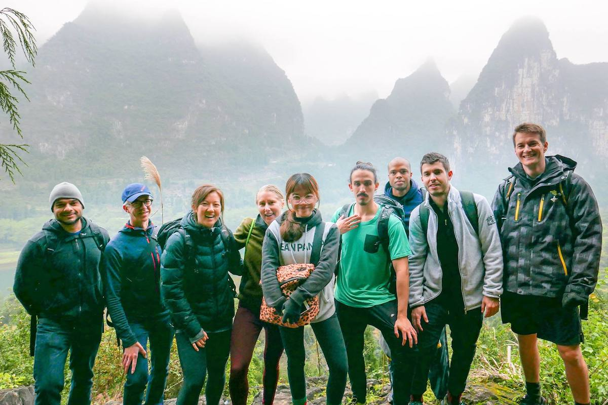 A group of CLI students and Yangshuo travel guides stand in front of karst mountains