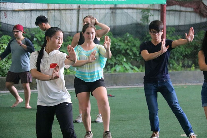a group of CLI students and teachers practicing tai chi.