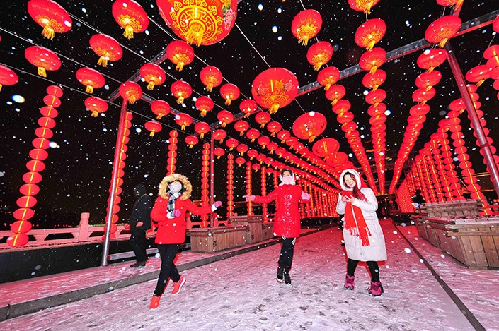three Chinese women walking under red Chinese lanterns in the snow during celebrations for the Year of the Ox