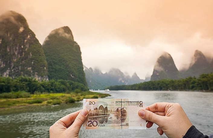a Chinese 20RMB note being held up against the scenic background depicted on it
