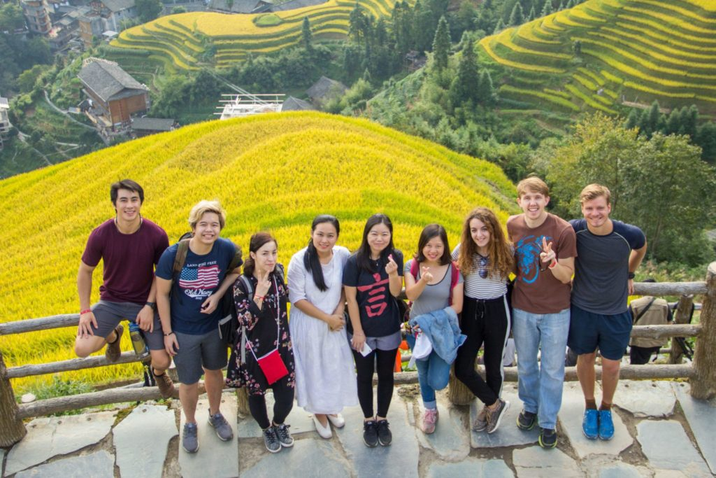A group of CLI students pose with yellow rice terraces in the background