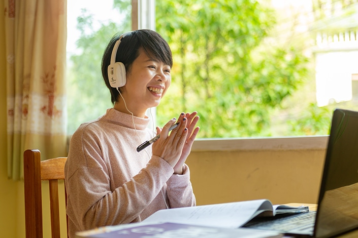 a CLI teacher claps while teaching Chinese online