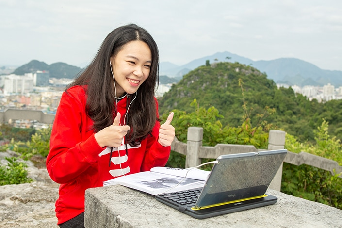 a CLI teacher giving a double thumbs up to an online student