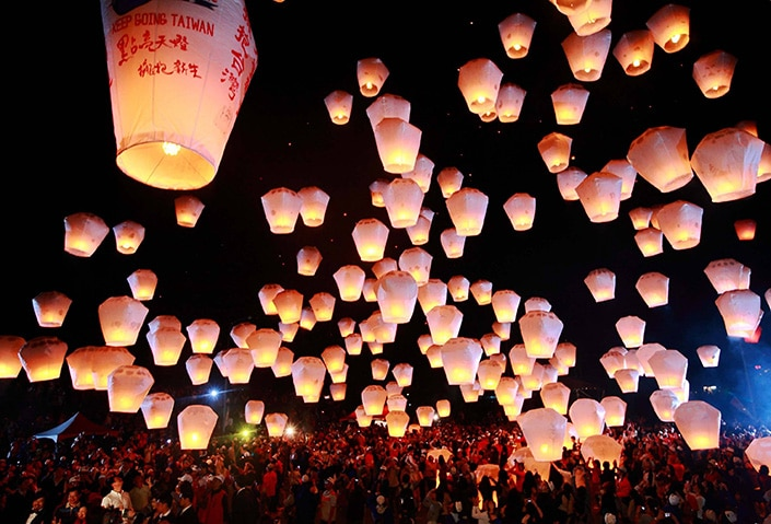 a photo of floating Chinese lanterns in the night sky