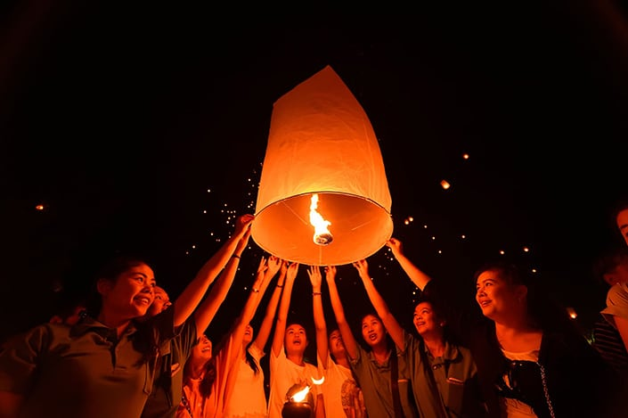 a photo of a group of people launching a floating Chinese lantern