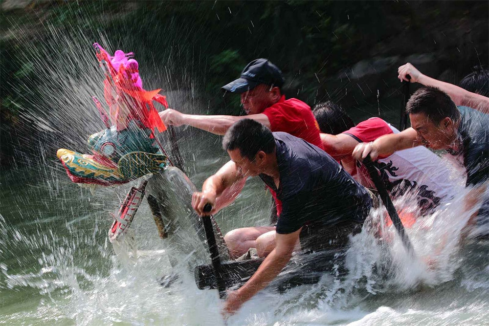photo of men rowing a dragon boat during Dragon Boat Festival, a popular Chinese holiday