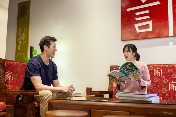 a student practices speaking with a teacher holding a Chinese textbook