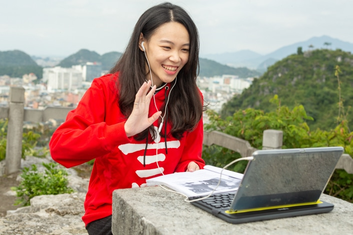 a Chinese teacher waves to her student while teaching online using a laptop