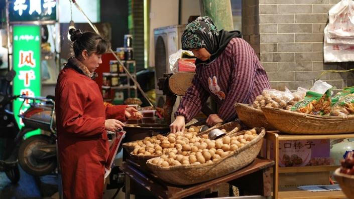 a Chinese Muslim woman selling walnuts