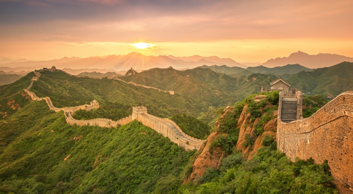 the sun rising over the Great Wall