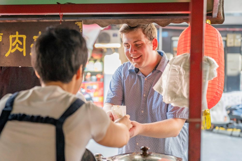a CLI student using Chinese renminbi to buy a snack from a Guilin street vendor