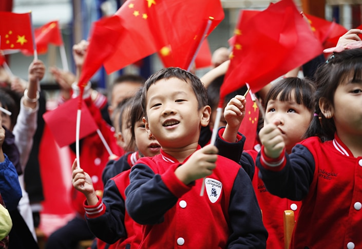 a photo of Chinese children waving red Chinese flags on National Day, an important Chinese holiday