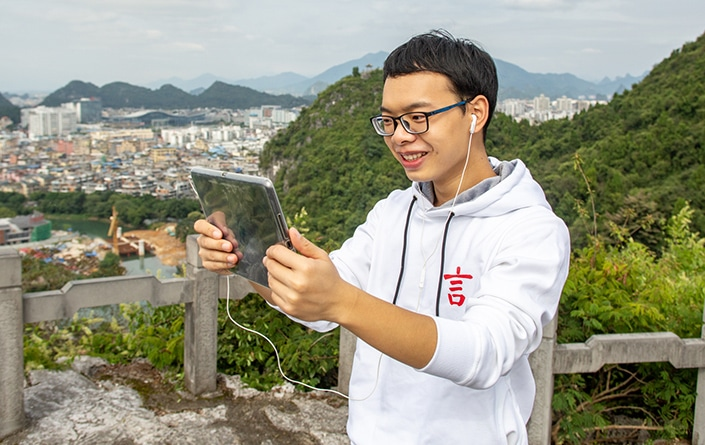 a CLI Chinese teacher talking with a student using a tablet on a mountaintop