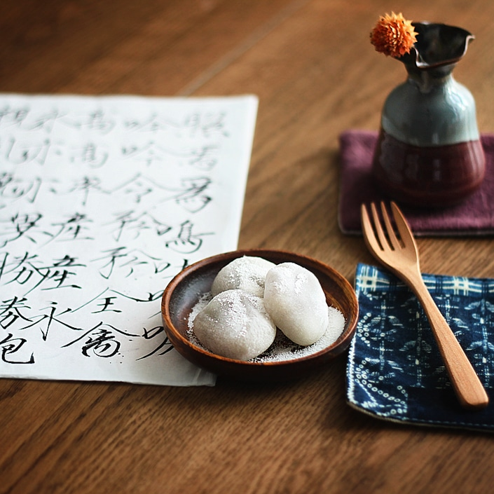 a plate of three rice dumplings sitting on a table with a wooden fork, a flower vase and a paper with Chinese calligraphy on it