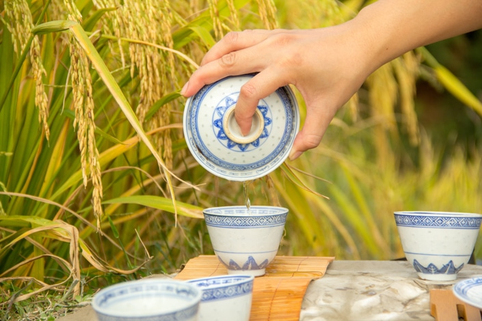a hand pouring traditional Chinese tea from a gaiwan teapot