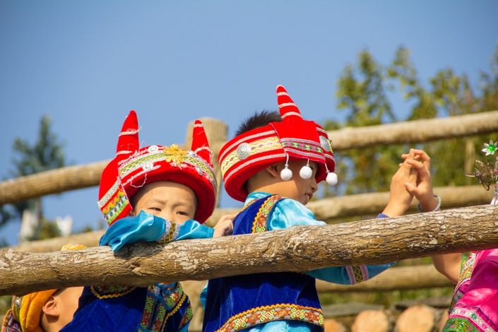 Two Chinese children wear traditional ethnic minority hats and clothes