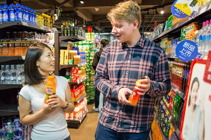 a teacher talks to her student about Chinese measure words while they hold bottles of juice in a supermarket