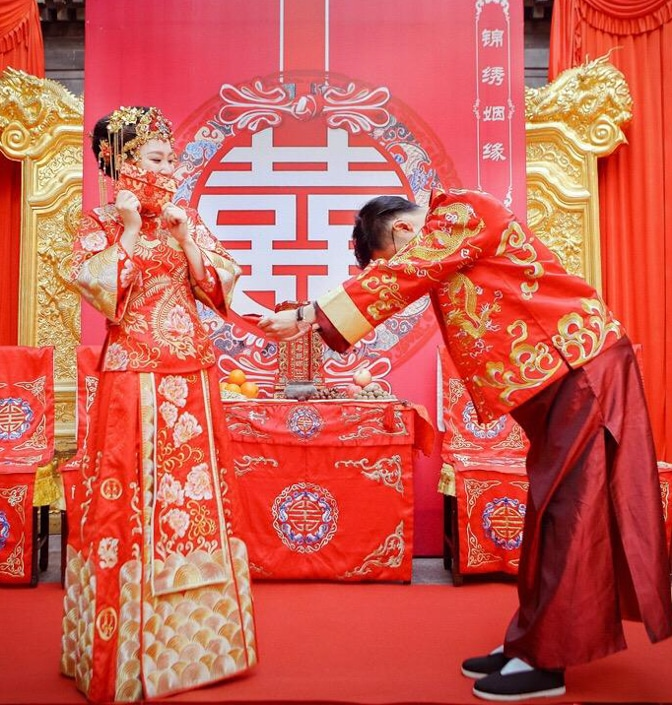 a bride and groom in traditional red and gold dress during a traditional Chinese wedding ceremony