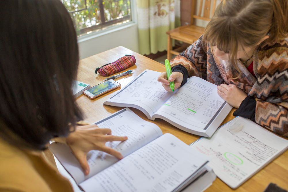a CLI student highlighting text in a Chinese textbook while her Chinese teacher looks on