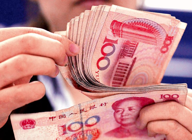 a woman's hand holding Chinese renminbi notes
