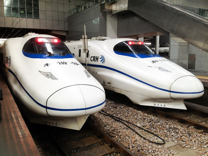 two Chinese fast trains sitting at a station