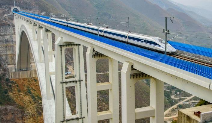 a Chinese fast train crossing a bridge over a ravine