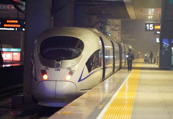 a Chinese train sits at platform number 15 as a conductor walks beside it