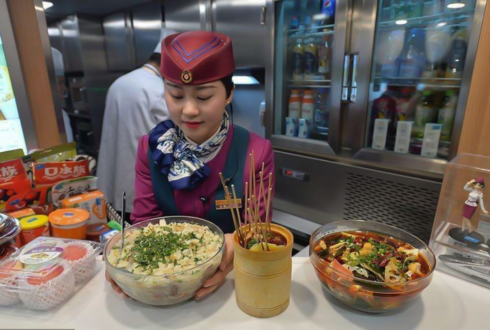 a Chinese female train attendant prepares food for passengers in a dining car