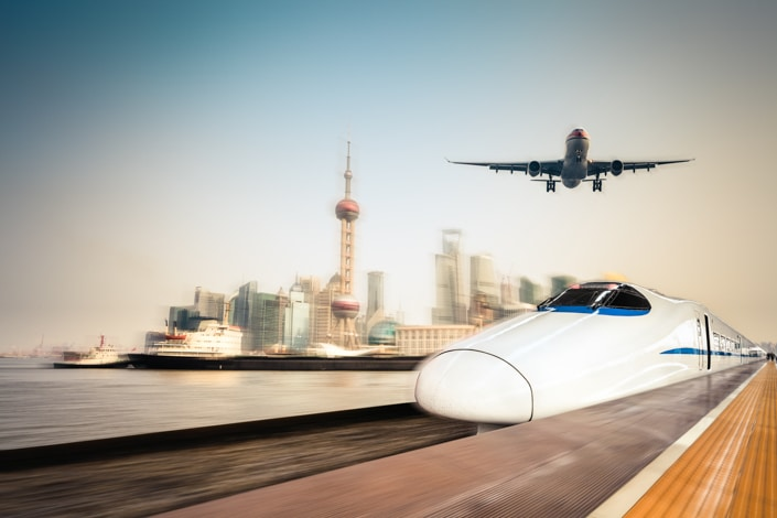 a Chinese fast train and airplane in the foreground with the Shanghai skyline in the background