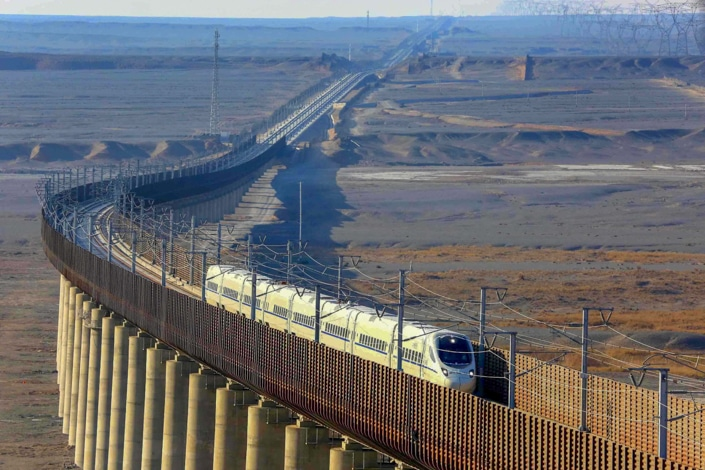 a Chinese train traveling through a desolate landscape