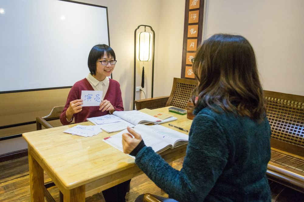 a teacher teaching a student using Chinese flashcards