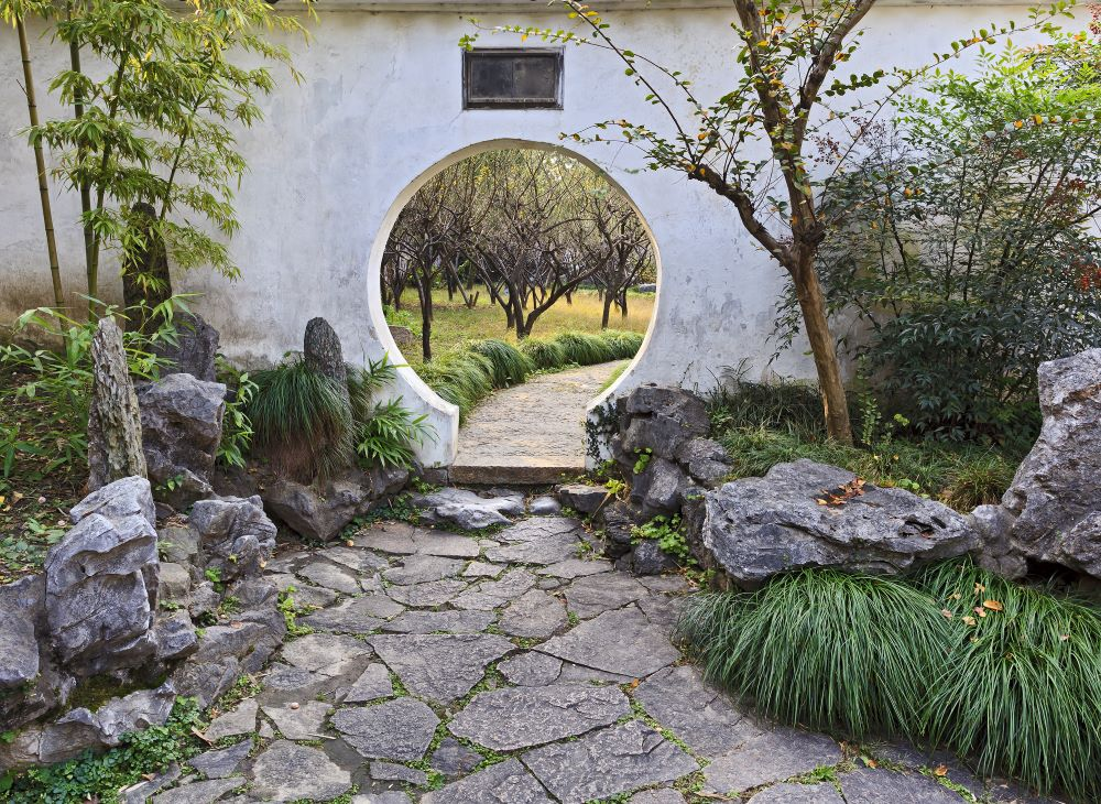 a round door in a wall in a traditional Chinese garden