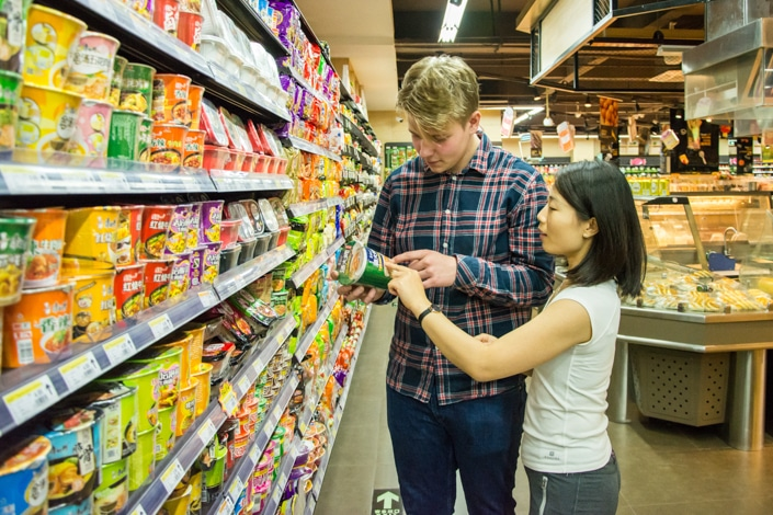 a blond man and a Chinese woman looking at some Chinese instant noodles in a supermarket
