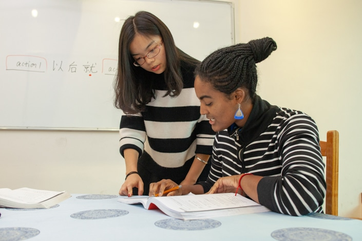 """a CLI teacher teaching a student in a striped shirt to say """"no"""" in Chinese"""