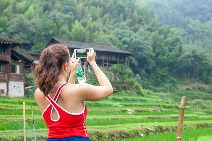 a brown haired girl with her back to the camera takes a picture of a rural scene in China on her phone