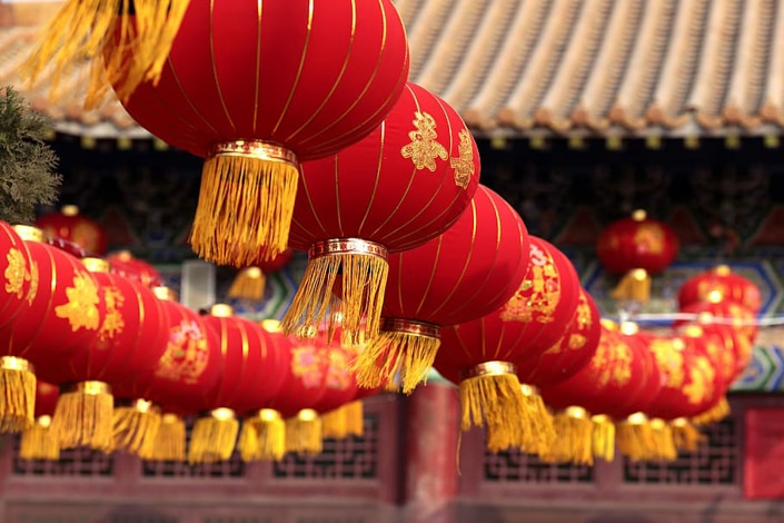 red Chinese lanterns with yellow tassels hanging in a row