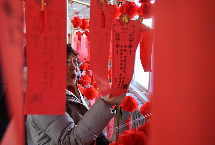 a woman looking at red Lantern Festival riddles