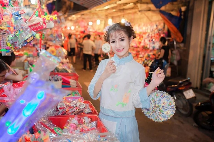 a Chinese girl buying souvenirs at an outdoor market