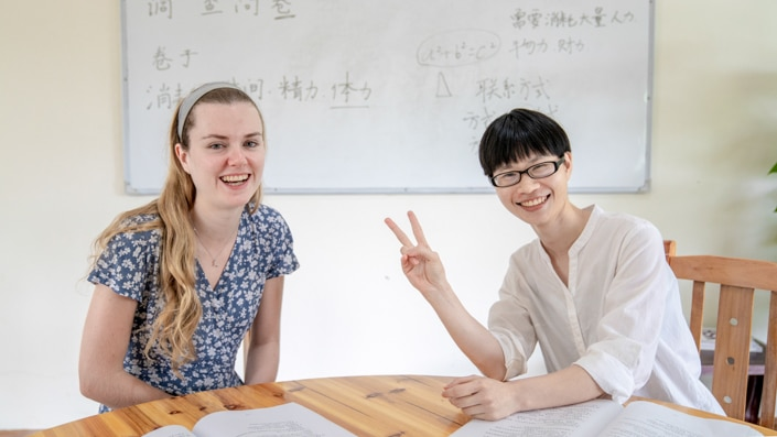 a blond student with her Chinese teacher sitting at a table in front of a whiteboard