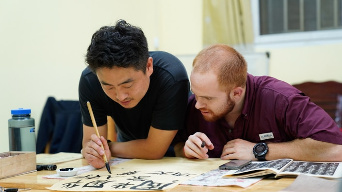 a red haired man watching a Chinese man write Chinese characters with a calligraphy brush