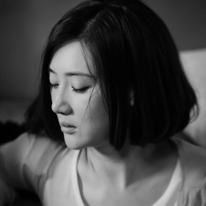 a black and white photo of a Chinese woman looking sad after experiencing pressure to conform with beauty standards in China