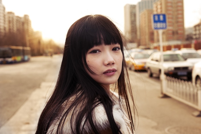 a photo of young Chinese woman who embodies standards of beauty in China looking back at the viewer